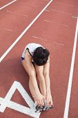 Female runner stretching legs on running track