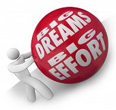 The words Big Dreams Big Effort on a heavy red ball being rolled uphill by a determined person or wo