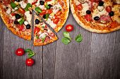 image of red meat  - Delicious italian pizzas served on wooden table - JPG