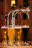 stock photo of spigot  - Four glasses of beer against beer tap - JPG