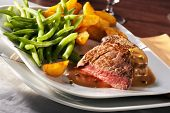 Steakhouse meal with rare beefsteak, potato wedges and green beans