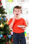 Little boy near Christmas tree eats cookies