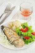 Peixe com legumes no prato e copo de vinho-de-rosa