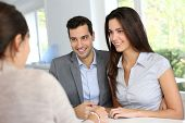 stock photo of contract  - Young couple signing financial contract - JPG