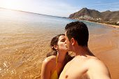 Young Couple Kissing In The Beach