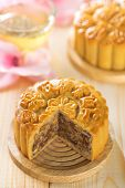 Traditional mooncakes on table setting with flower tea.  Chinese mid autumn festival foods. The Chin