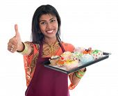 Happy Traditional Indian woman in sari baking bread and cupcakes and showing thumb up, wearing apron holding tray isolated on white.