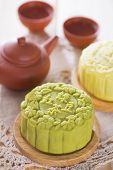 Snowy skin mooncakes.  Traditional Chinese mid autumn festival food and tea set. The Chinese words on the mooncakes means green tea with red bean paste and lotus paste, not a logo or trademark.