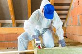 stock photo of attic  - Worker in overall is cutting insulating material with gloves and knife - JPG