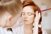 stock photo of barber  - Stylist makes makeup bride on the wedding day - JPG