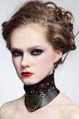 Portrait of young beautiful girl with stylish hairdo and fancy steampunk collar