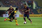 KUALA LUMPUR - AUGUST 10: Barcelona's Adriano (maroon/blue) dribbles past Malaysia's defenders (yell