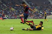 KUALA LUMPUR - AUGUST 10: FC Barcelona's Cristian Tello (maroon/blue) dribbles the ball in a match vs Malaysia at the Shah Alam Stadium on Aug 10, 2013 in Kuala Lumpur, Malaysia. Barcelona wins 3-1.