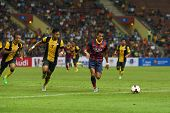 KUALA LUMPUR - AUGUST 10: FC Barcelona's Alexis Sanchez (maroon/blue) leads in attack against the Malaysian team at the Shah Alam Stadium on August 10, 2013 in Malaysia. FC Barcelona wins 3-1.