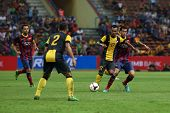 KUALA LUMPUR - AUGUST 10: Malaysia's Amri Yahya (17) defends Barcelona's Sergio Busquets (maroon/blue) attack in a game at the Shah Alam Stadium on Aug 10, 2013 in Malaysia. FC Barcelona wins 3-1.