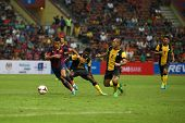 KUALA LUMPUR - AUGUST 10: FC Barcelona's Alexis Sanchez (maroon/blue) leads in attack against Malaysia at the Shah Alam Stadium on August 10, 2013 in Malaysia. FC Barcelona wins 3-1.