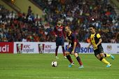 KUALA LUMPUR - AUGUST 10: FC Barcelona 's Andres Iniesta (maroon/blue) controls the ball, watched by