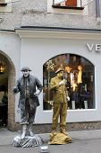 SALZBURG, AUSTRIA - AUGUST, 2012 : Street performers - Gold and Silver men pose on the shopping stre