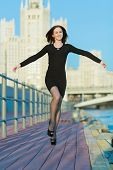 A young woman in a black dress jumping arms outstretched to the sides on the waterfront