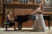 stock photo of singer  - Woman pianist plays the piano and beautiful singer stands next - JPG