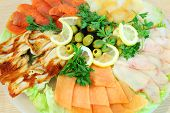 Grilled and smoked fish, smoked meat, lemons and olives on large plate.