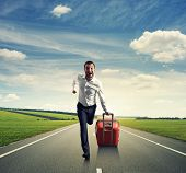 happy businessman running with suitcase on the road