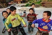 Chinese Boys Riding Bikes On The Dong Ethnic Village Peoples.