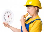 Young happy lady as a construction worker is biting donut while holding big clock, lunchtime concept