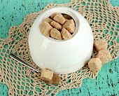 Unrefined sugar in white sugar bowl on wooden background