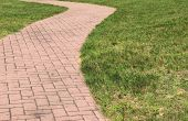 picture of manicured lawn  - Pretty red brick walkway that curves across neatly manicured lawn - JPG