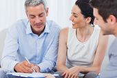 stock photo of contract  - Client signing a contract with wife held by salesman on couch - JPG