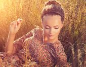Beauty Romantic Girl Outdoors. Beautiful Teenage Model girl Lying on the Field in Sun Light. Autumn.