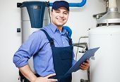 stock photo of pipefitter  - Smiling technician servicing an hot - JPG