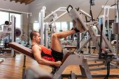 stock photo of squatting  - Man working out in a fitness club - JPG