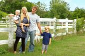 Happy Family Outside By Horse Pasture