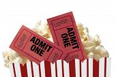 foto of matinee  - Close up shot of red movie tickets in a tub of delicious popcorn and shot on white background - JPG