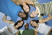 picture of huddle  - Directly below shot of young friends forming huddle against blue sky - JPG