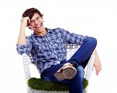 Young man in checkered shirt and blue jeans sitting in white chair with hand near his head and laugh