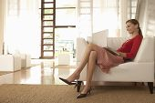 Full length of young businesswoman using laptop while sitting on chair in office lobby