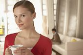 Portrait of confident businesswoman holding coffee cup in office lobby