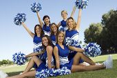 stock photo of cheerleader  - Portrait of confident cheerleaders holding pompoms on field - JPG