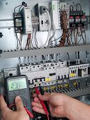 stock photo of contactor  - Engineer makes maintenance of power network automation system - JPG