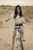 Fashion art style photo ( soft and grainy ) of boho Californian girl riding beach bike.