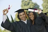 stock photo of graduation gown  - Portrait of happy students holding diplomas on graduation day - JPG
