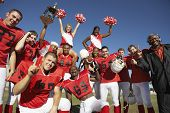 stock photo of cheerleader  - Portrait of happy football team with cheerleaders and coach celebrating success on field - JPG