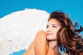 beautiful angel woman with white wings against blue sky small amount of grain added