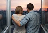 Young couple on the balcony watching sunset