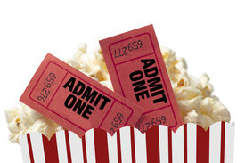 stock photo of matinee  - Close up shot of red movie tickets in a tub of delicious popcorn and shot on white background - JPG