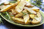 Fried potatoes with rosemary and sea salt flakes, on a green plate. Oven baked wedges.
