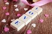 pic of scrabble  - love word made of scrabble letters and little heart shapes for valentine on wooden table - JPG